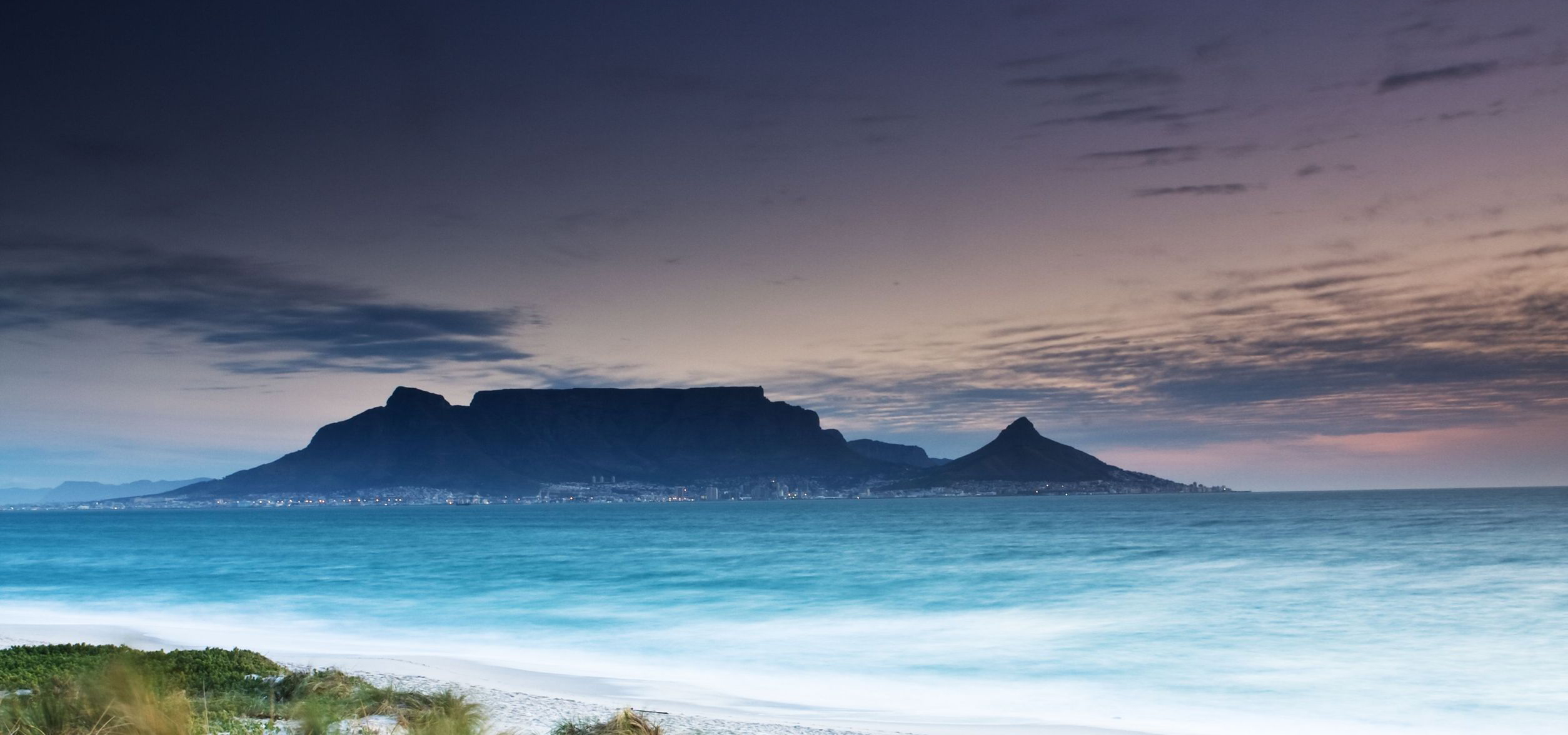3712141 – table mountain from milnerton beach with grass in the foreground